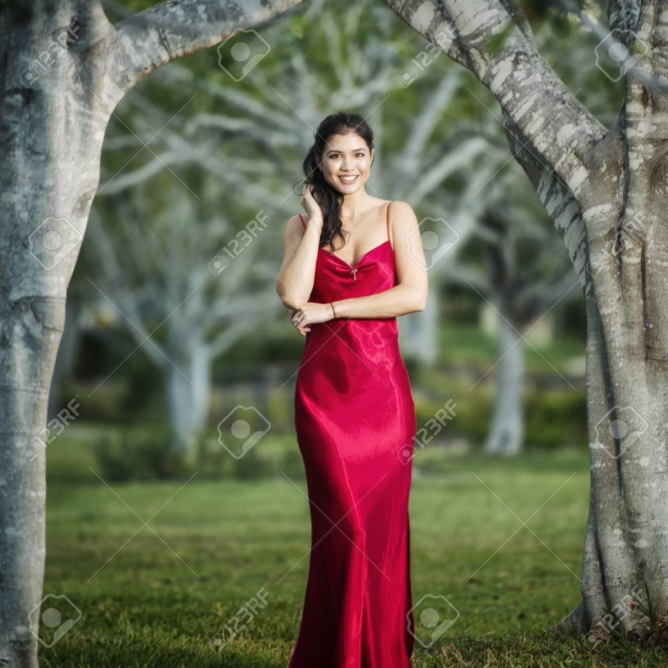 ac16379d5582b Banque d images - Belle jeune femme portant une longue robe de cérémonie en  soie rouge dans les jardins l après-midi.