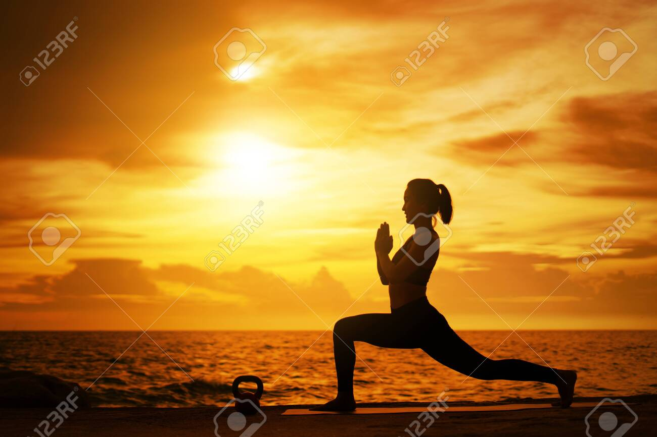 woman practicing yoga during surrealistic sunset at the seaside. healthy concept and workout. - 128366566