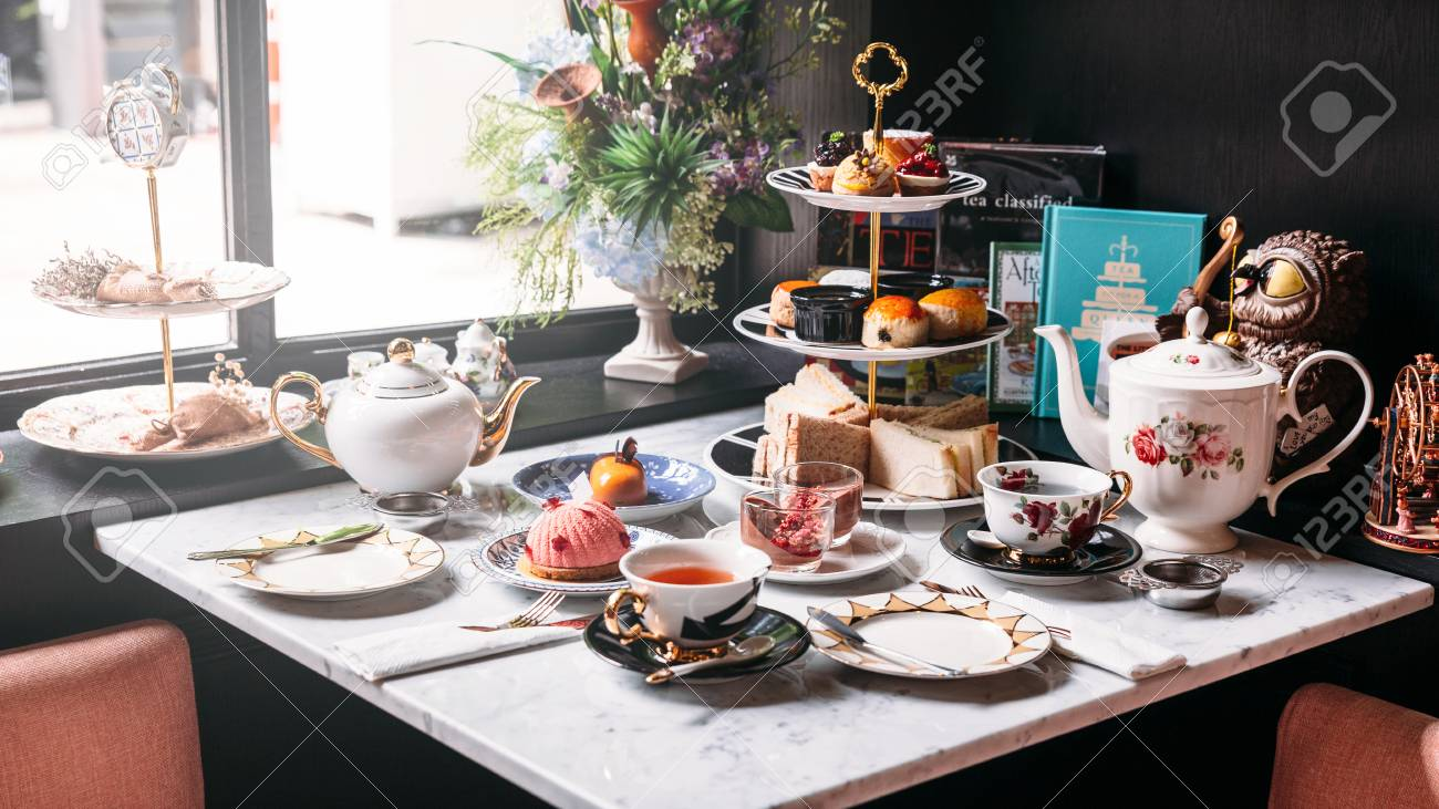 English afternoon tea set including hot tea, pastry, scones, sandwiches and mini pies on marble top table. - 115251073