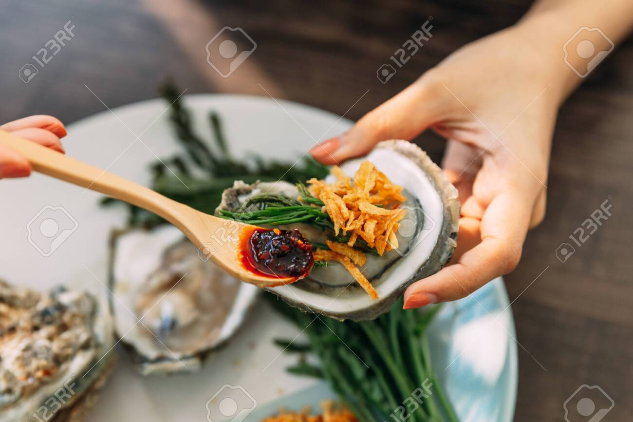 Fresh Oyster in shell in hand that topping with fried shallot, chili paste, Acacia Pennata and Thai style seafood sauce. - 131604507