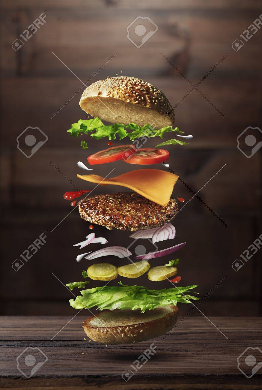 Classic burger ingredients flying on a wooden brown background - 64432868