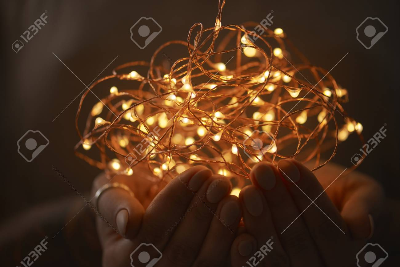Well known Hands Of A Girl Holding A Garland Of Christmas Lights On A Dark  QZ03