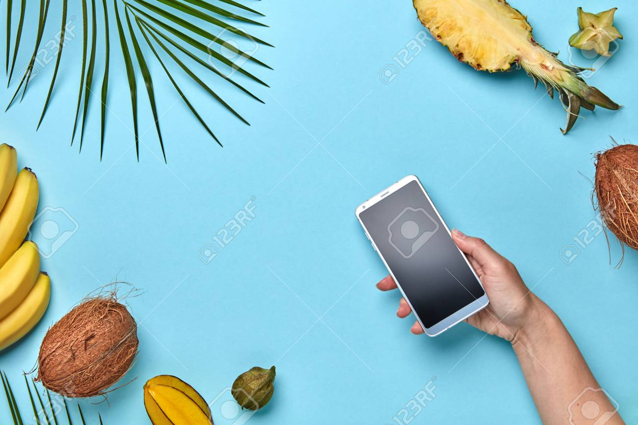316d564a5 A womans hand is holding a mobile phone on a blue background with space for  text. Purchase of products on the Internet.
