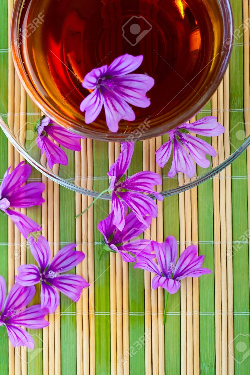 Teacup with saucer and flowers on the straw napkin.. Stock Photo - 13579628