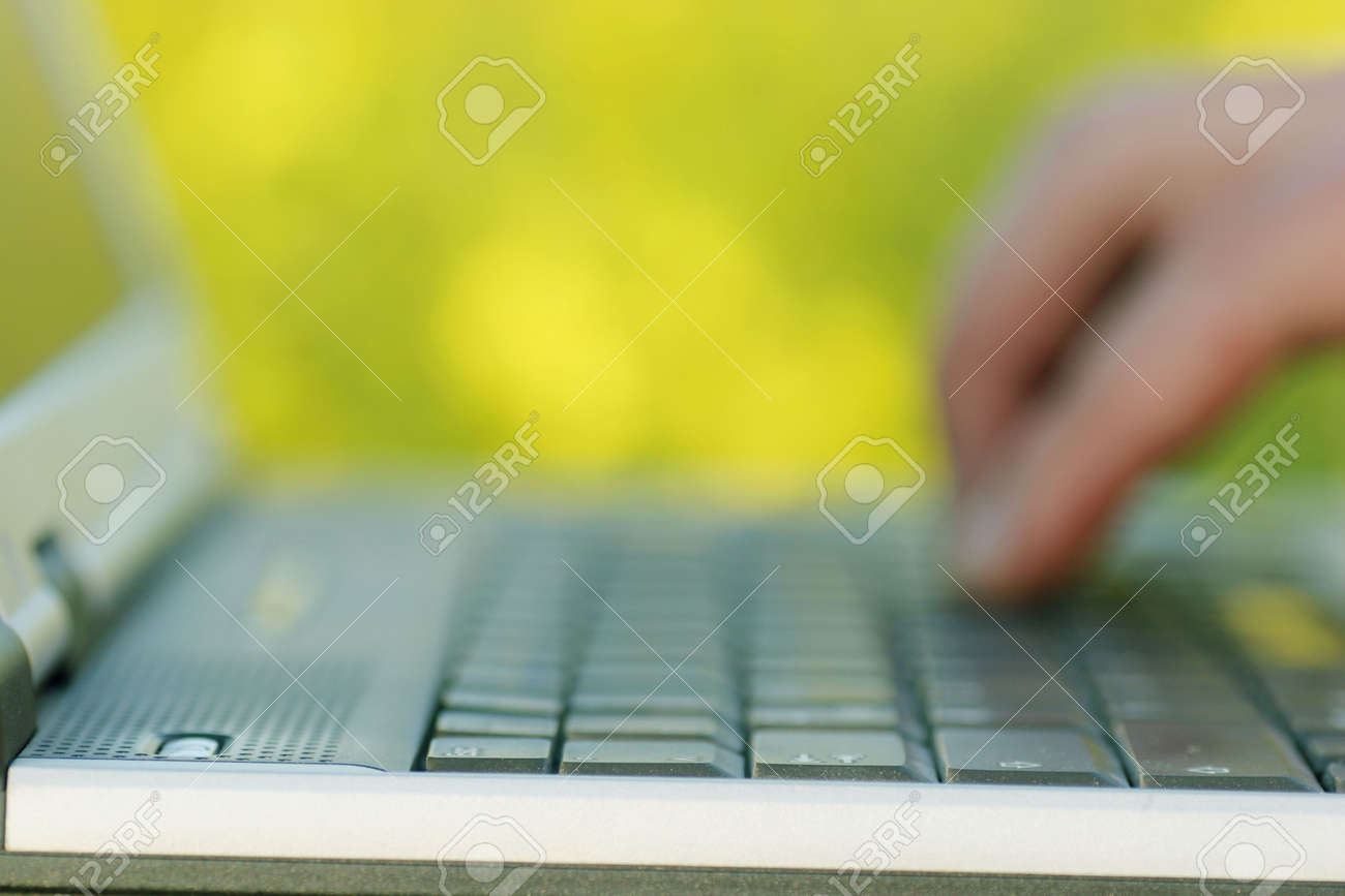 Blurred hand working on a laptop with yellow flowers in the background. (The focus is on the foreground on the edge of the laptop) Stock Photo - 443886