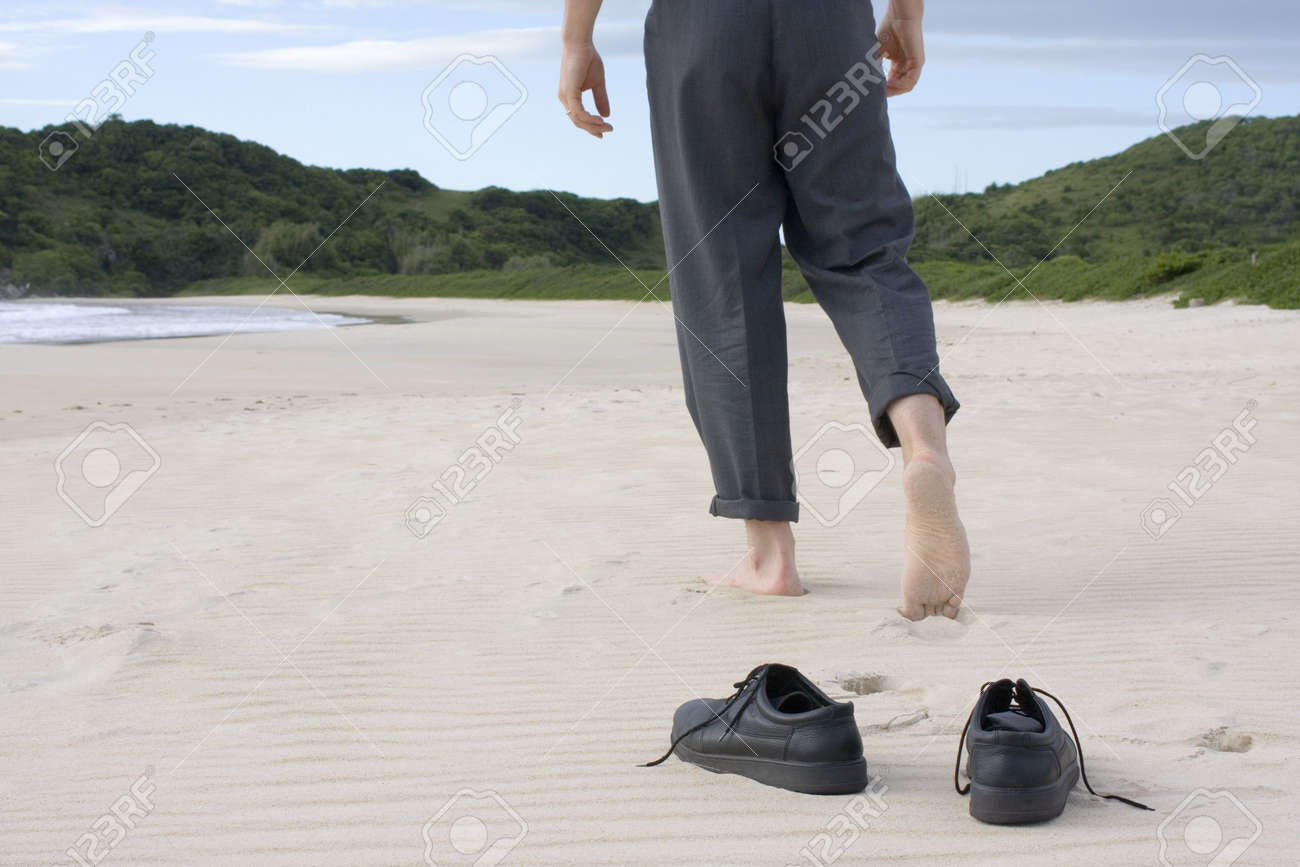 745d6fe80 Businessman walking barefoot on a empty beach. Focus on his shoes in the  foreground Stock