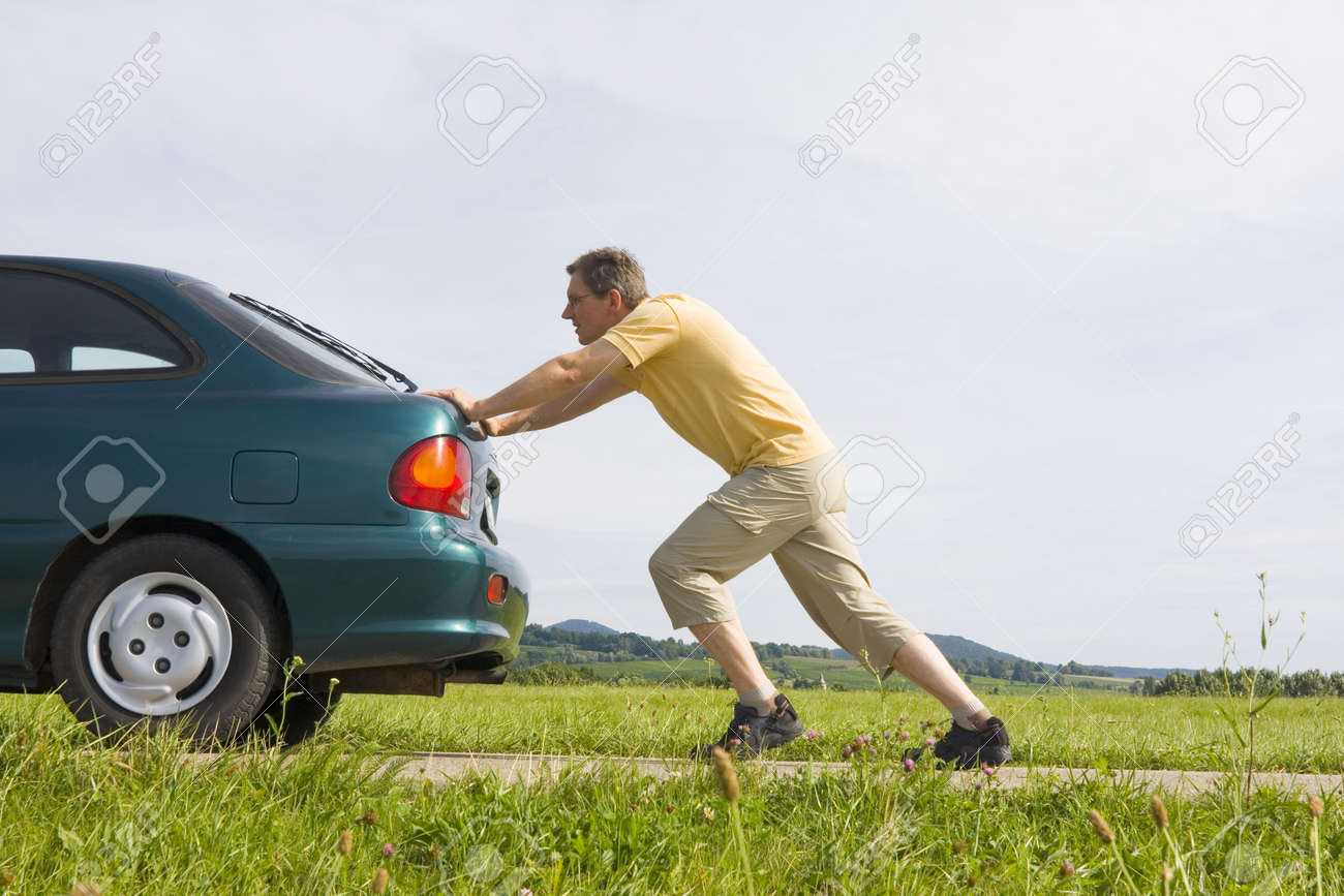 man pushing a car with empty gas tank stock photo picture and