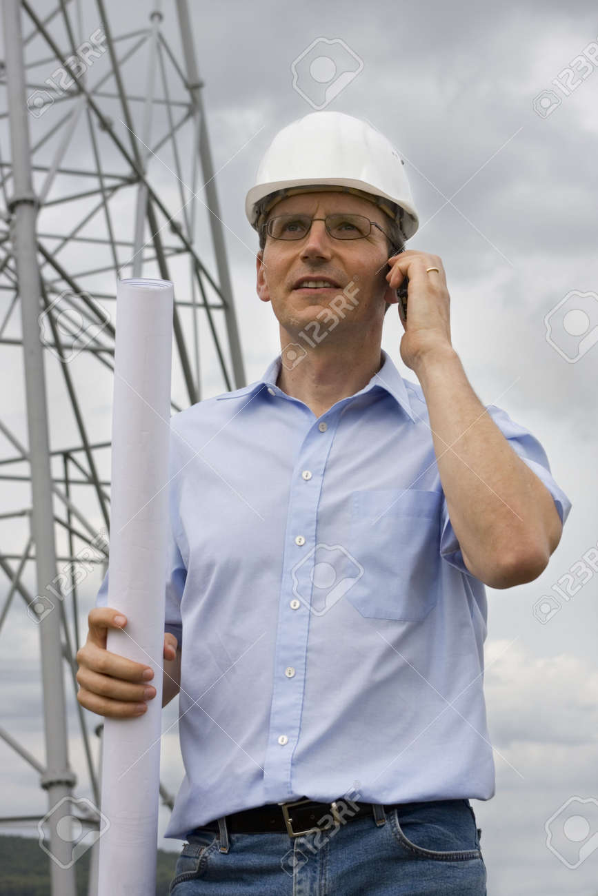 Engineer with plan in his hand talking on cell phone on construction side Stock Photo - 5469575