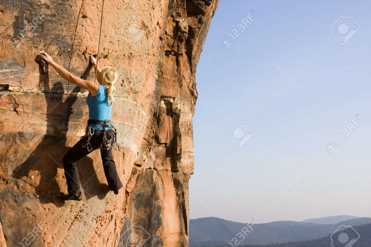 Young woman climbing a rock of sandstone Stock Photo - 5755456