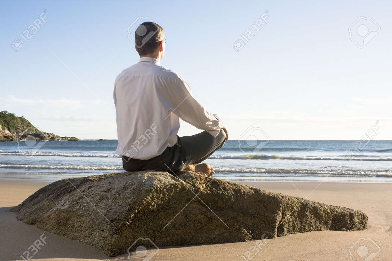 Businessman meditating on a sunny beach in the morning Stock Photo - 6956954