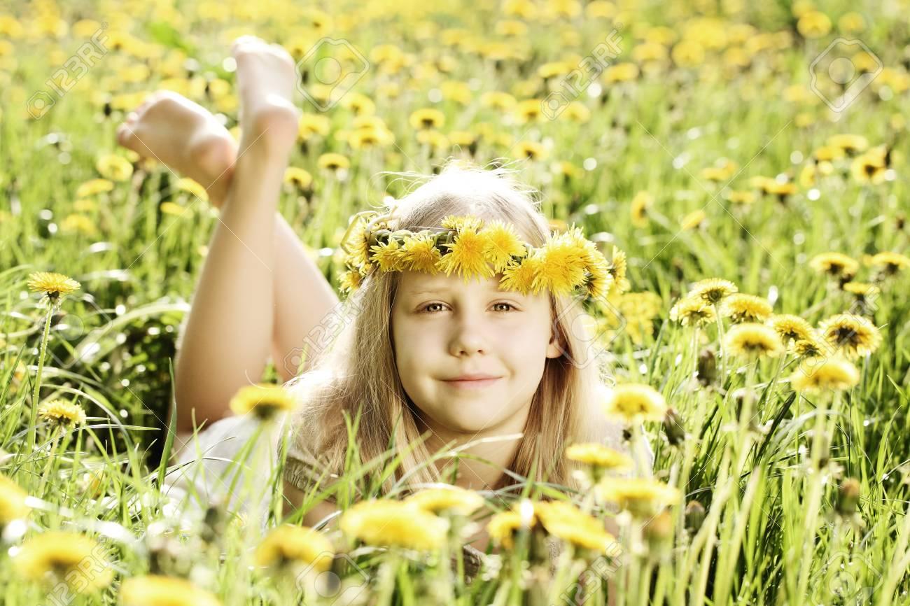 Cute Little Girl On Sunny Lighting Background Of Green Grass Stock