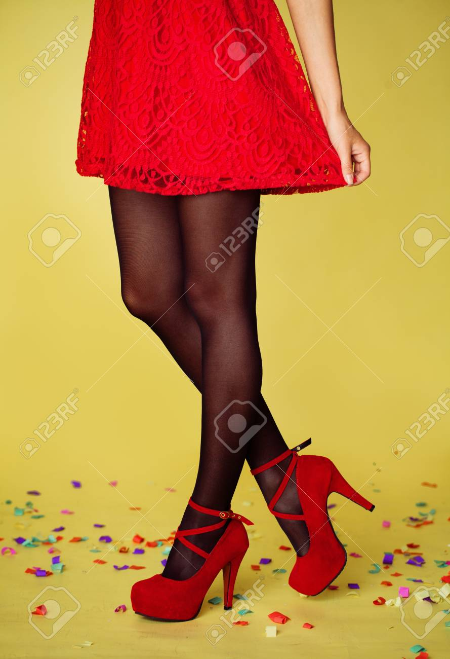 0b63d800620 Beautiful female legs in black tights and red high heels shoes on yellow  holiday background Stock