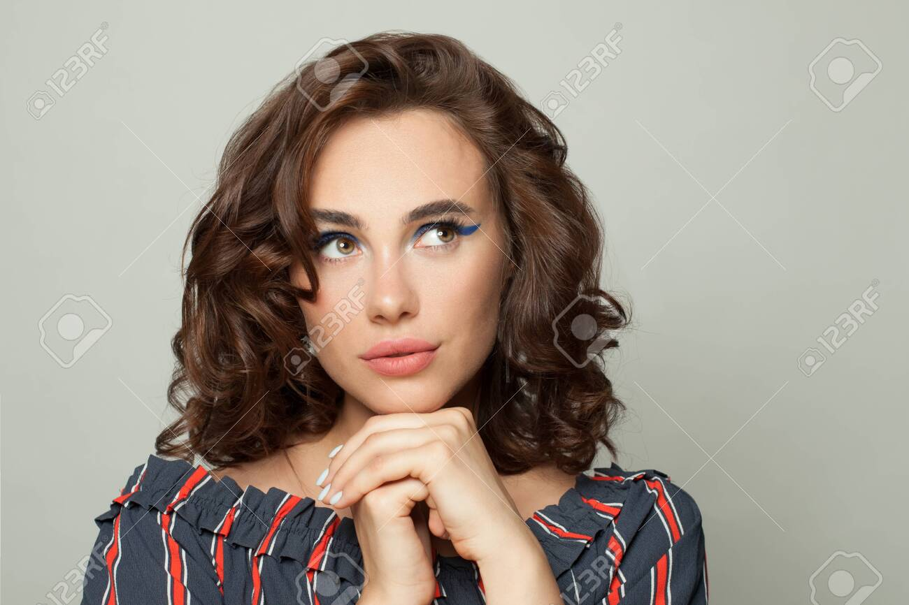 Attractive woman with brown curly bob hairdo looking up aside on white - 151463633