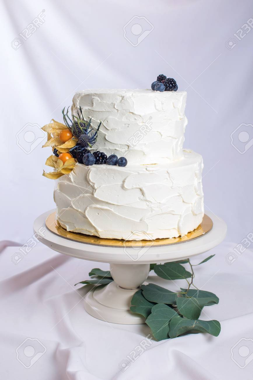Two Tiered White Cream Cake Decorated With Berries In A Rustic