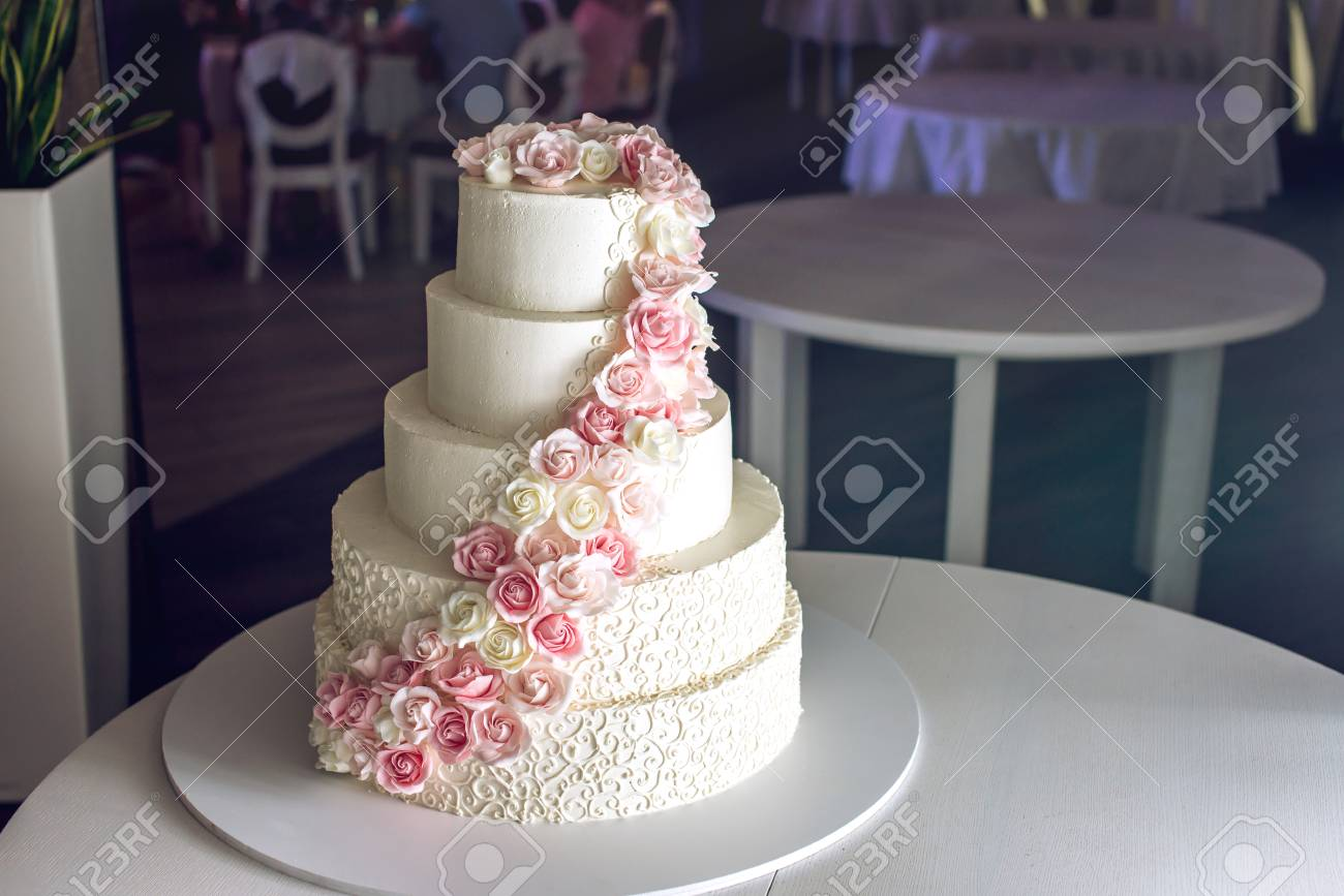 Un Grand Gateau De Mariage A Plusieurs Niveaux Decore De Roses Roses Sur La Table Du Restaurant Le Concept Des Desserts Festifs