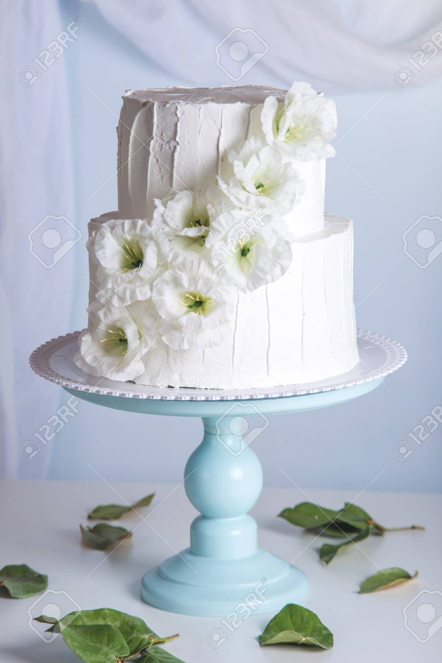 Attractive wedding cake with blue flowers adornment the wedding white bunk wedding cake decorated with flowers on a blue bookcase izmirmasajfo Images