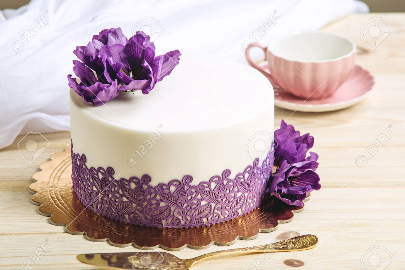 A Beautiful Home Wedding Cake Decorated With Purple Peonies In ...