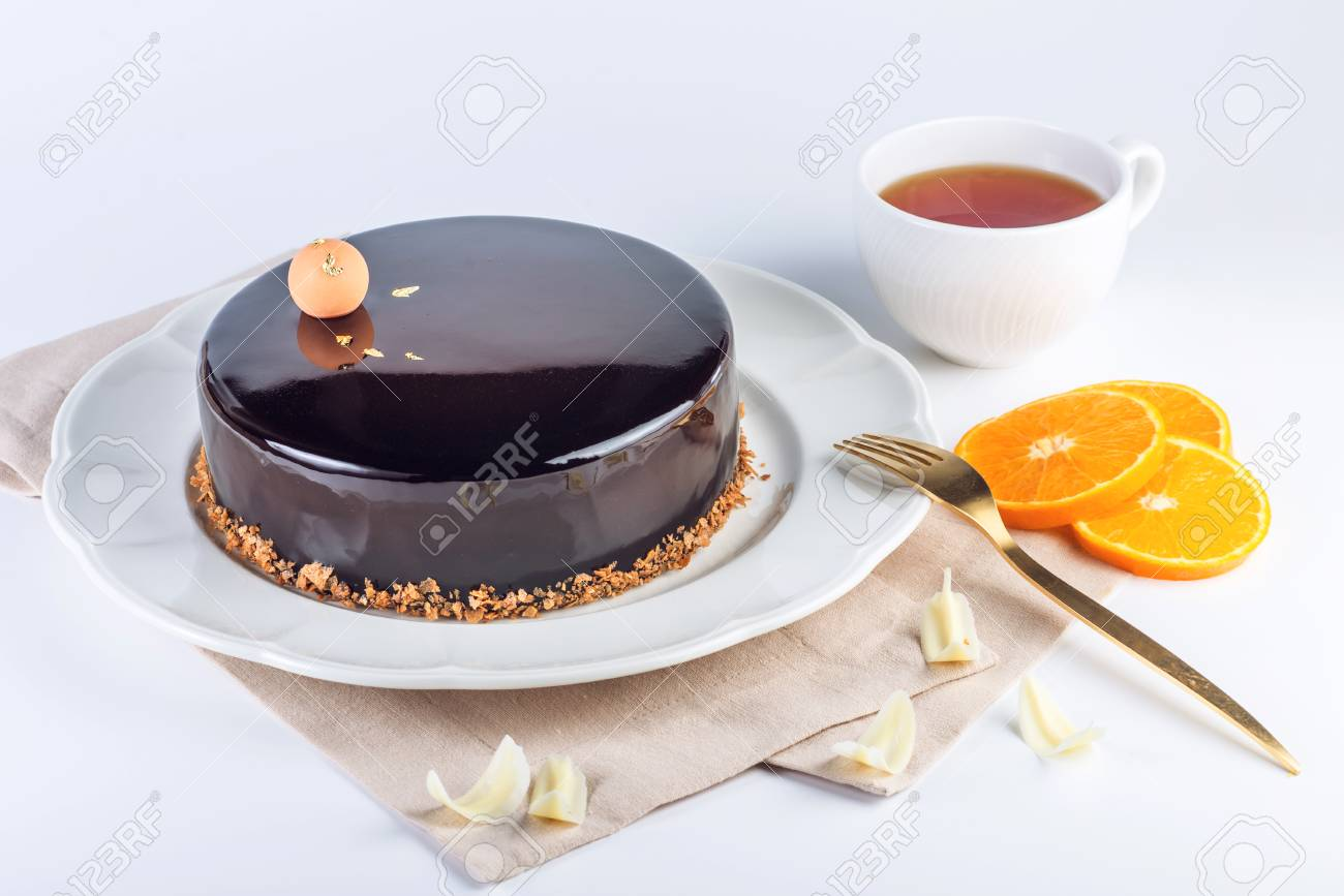 Beautiful truffle cake with orange covered with glossy dark chocolate