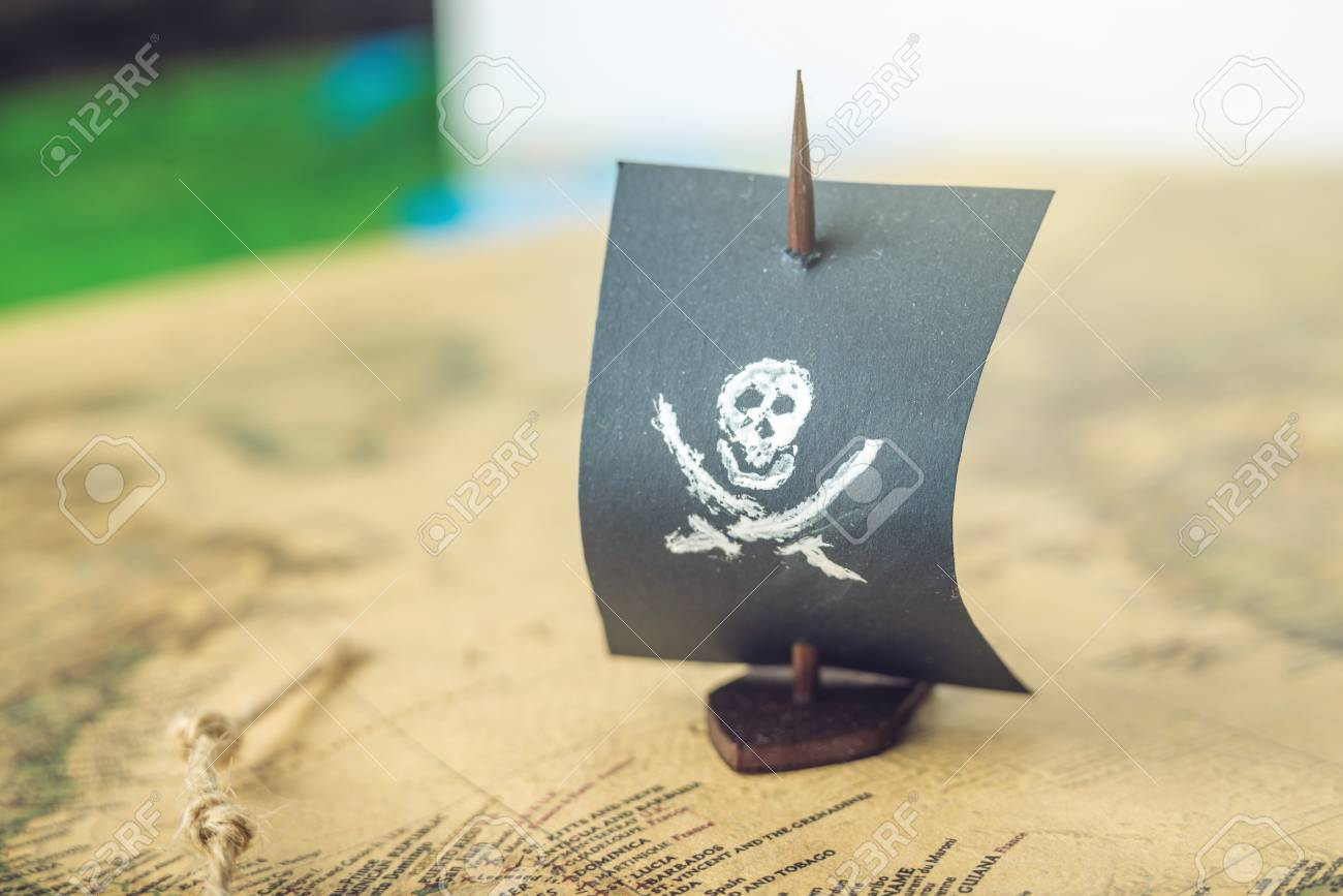 Toy boat pirate flag skull and bones on the world map of the stock stock photo toy boat pirate flag skull and bones on the world map of the playing field handmade board games the concept of piracy gumiabroncs Image collections