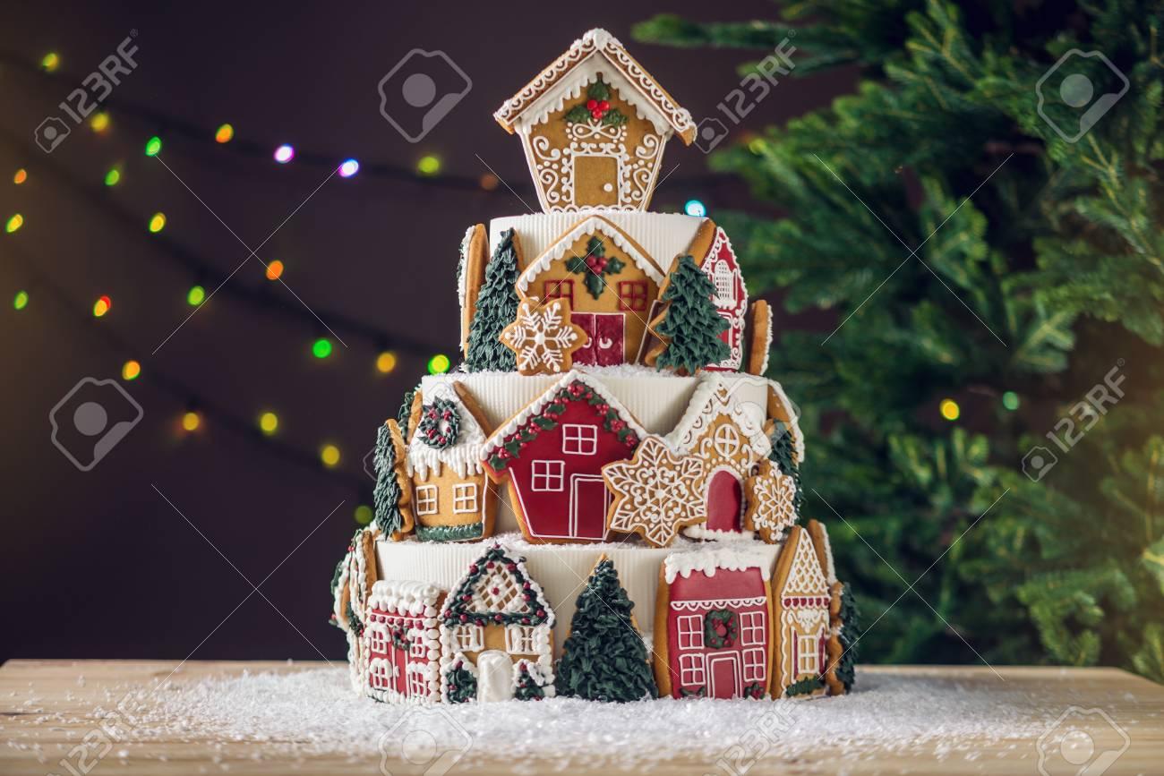 Torte Decorate Per Natale grande torta di natale a più livelli decorata con biscotti di panpepato e  una casa in cima. albero e ghirlande sullo sfondo. il concetto di dessert