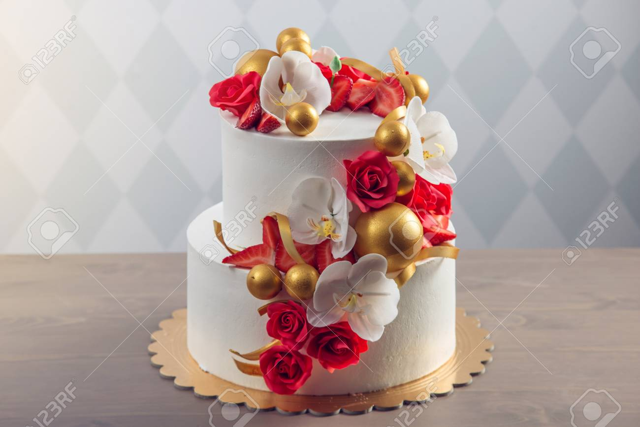 A Beautiful Two Tiered White Wedding Cake Decorated With Red Stock