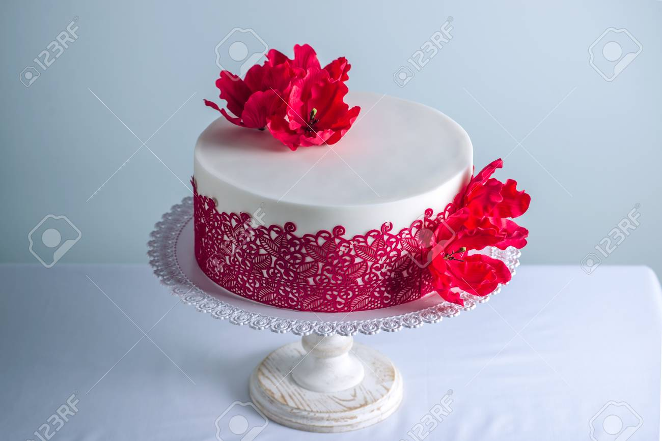 Beautiful White Wedding Cake Decorated With Flowers Sugar Poppies And Red Pattern Ornament On The Table