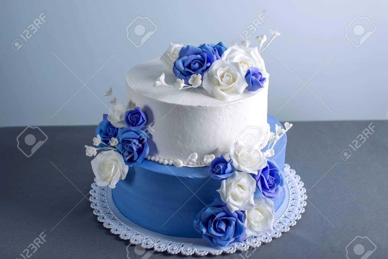 Beautiful two tiered white and blue wedding cake decorated with beautiful two tiered white and blue wedding cake decorated with flowers sugar roses on the table izmirmasajfo