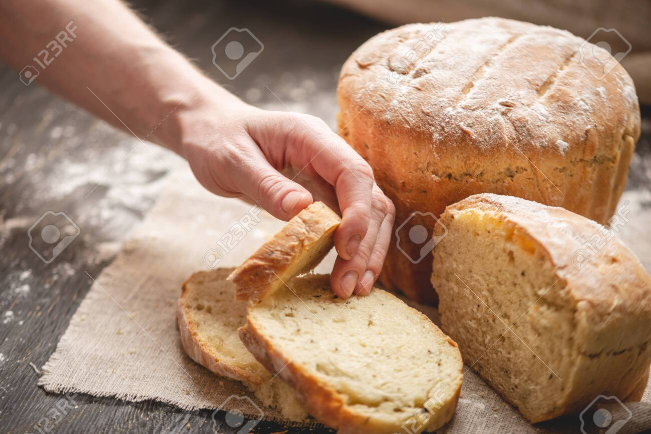 Women's hands breaking homemade natural fresh bread with a Golden crust on a napkin on an old wooden background. The concept of baking bakery products - 120638880