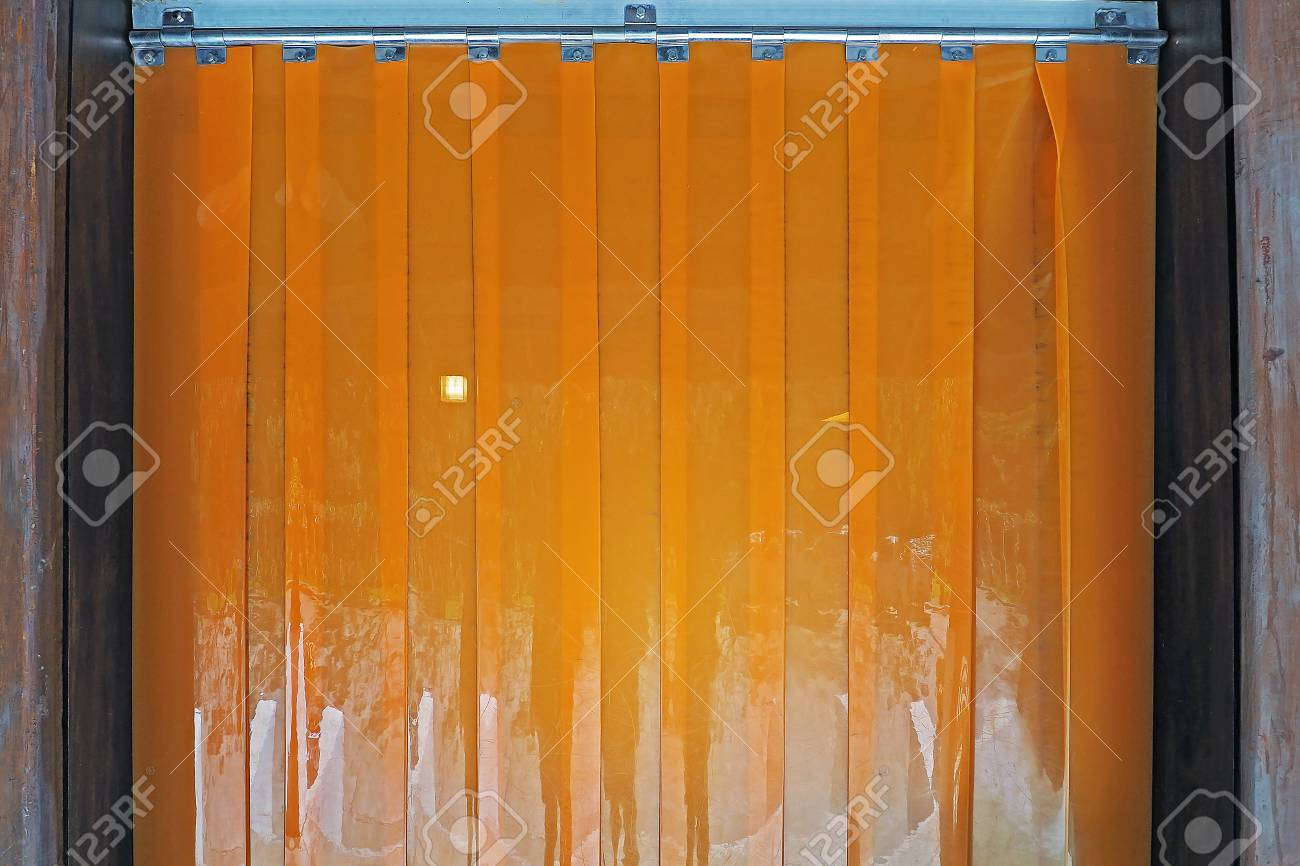 Orange Color Industrial Warehouse Plastic PVC Strip Curtains Hanging At The Wood Door Stock Photo