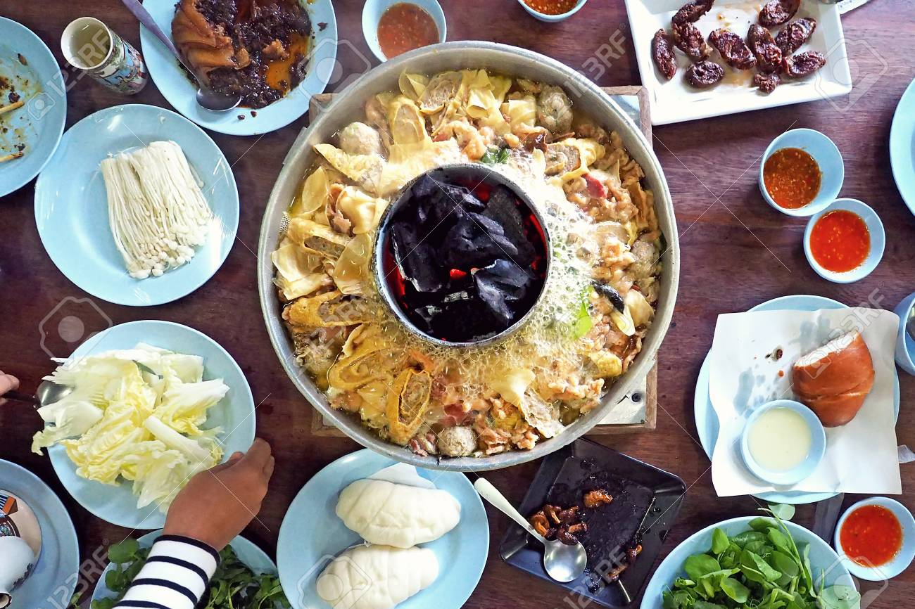 family enjoy eating traditional local asian chinese yunnan style grand  hotpot on table center - photo