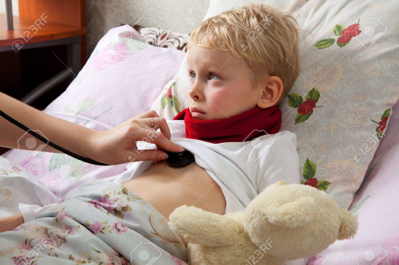 The little boy is sick. He lies in bed. Red scarf is on his neck. Teddy Bear is in his hand. Somebody explorers boys lungs with a stethoscope. Stock Photo - 16574071