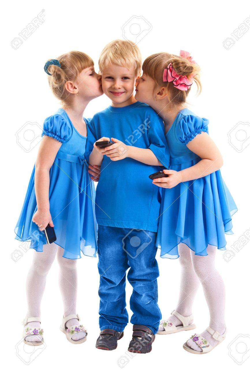 Two girls which twins are kissing a boy which is sending messages or is playing on his cell phone on white background. All they dressed in blue. Stock Photo - 17455045