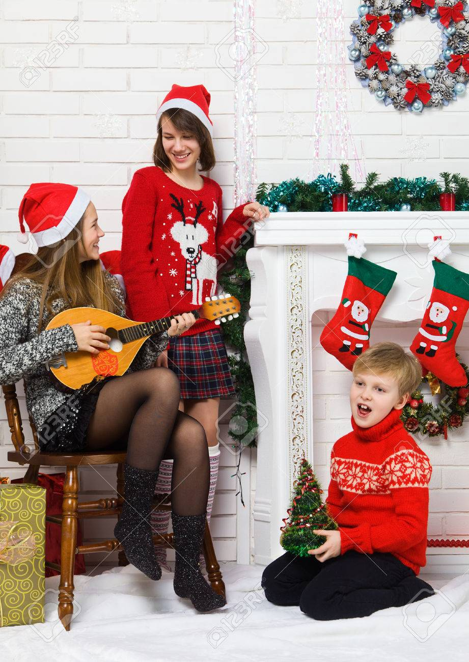 Happy brother and sisters are singing holiday songs near the