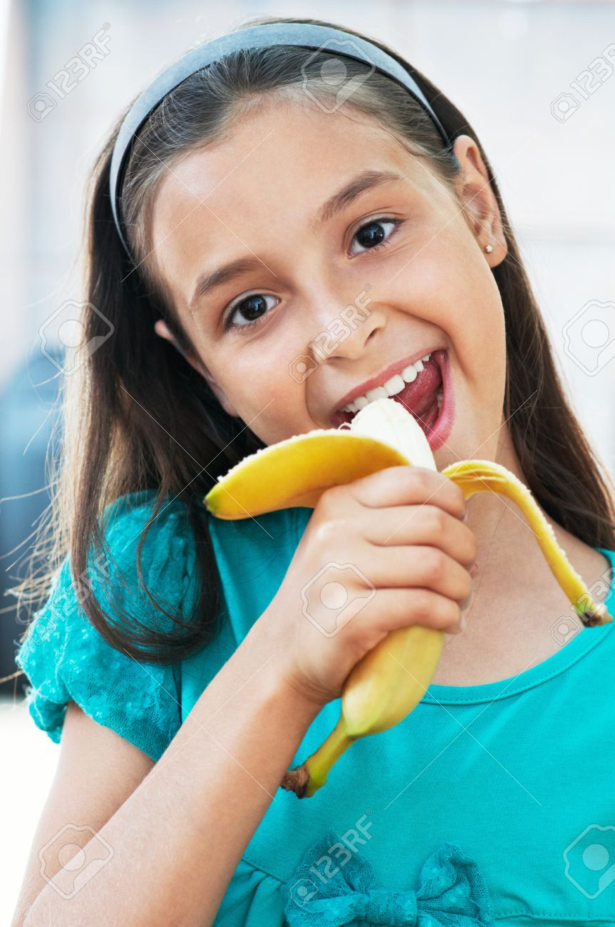 girls eating bannana Stock Photo - cute caucasian girl eats an banana