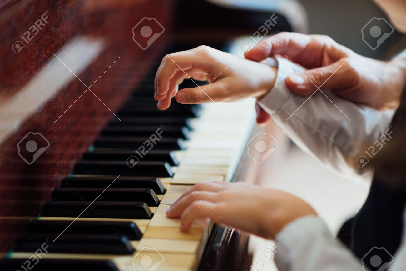 experienced master piano hand helps the student, close-up - 53687592