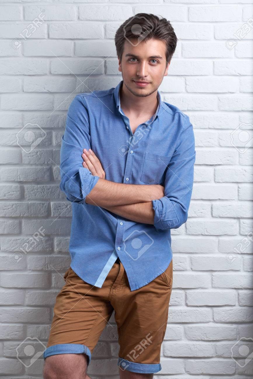 7ca9290fac Uomo sorridente è rimanere sullo sfondo di mattoni in studio in camicia blu  e pantaloni marroni