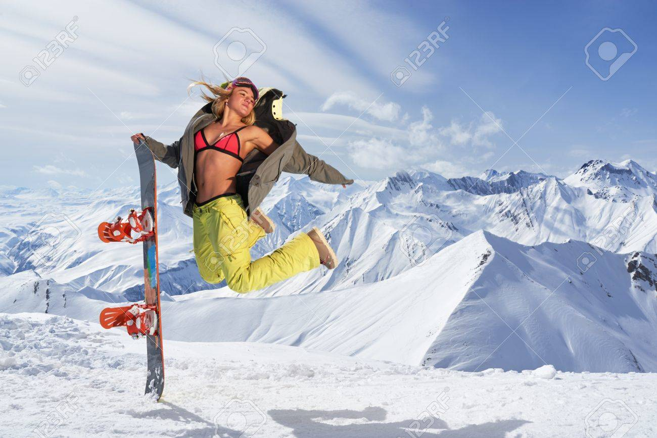 e79dfb414ebd Smiling woman with snowboard jumping in mid air against of snowy mountains.Wearing  bikini top
