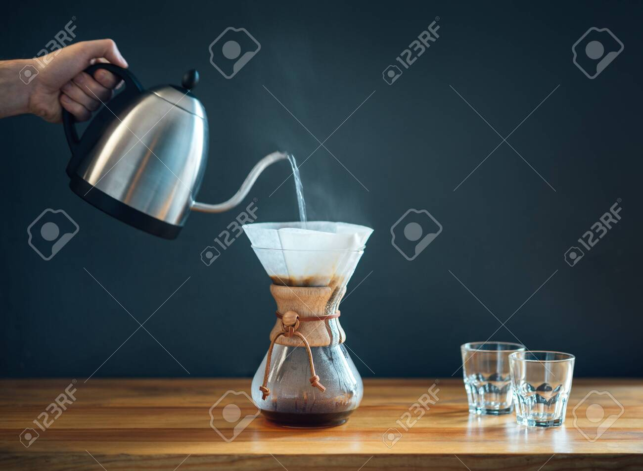 making coffee by an alternative method, pouring hot water from kettle into a glass decanter on a wooden table and gray background, minimalism side-view - 135265265