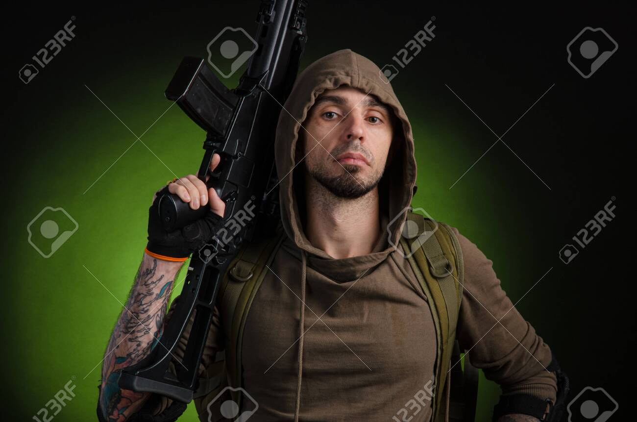 man Stalker with a gun with an optical sight and a backpack on a dark background - 132316747