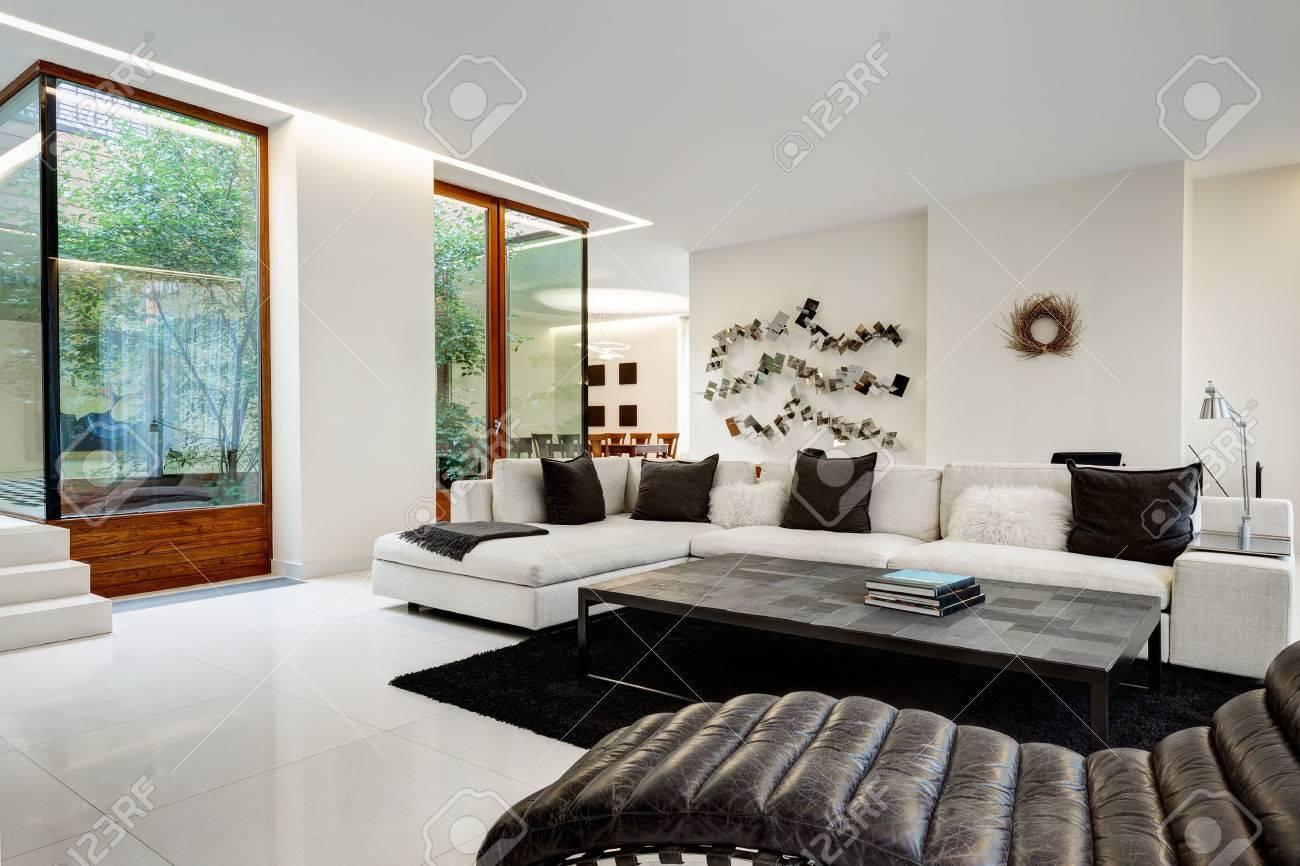 Grand et confortable salon avec un canapé blanc dans une maison de luxe  avec un jardin d\'hiver