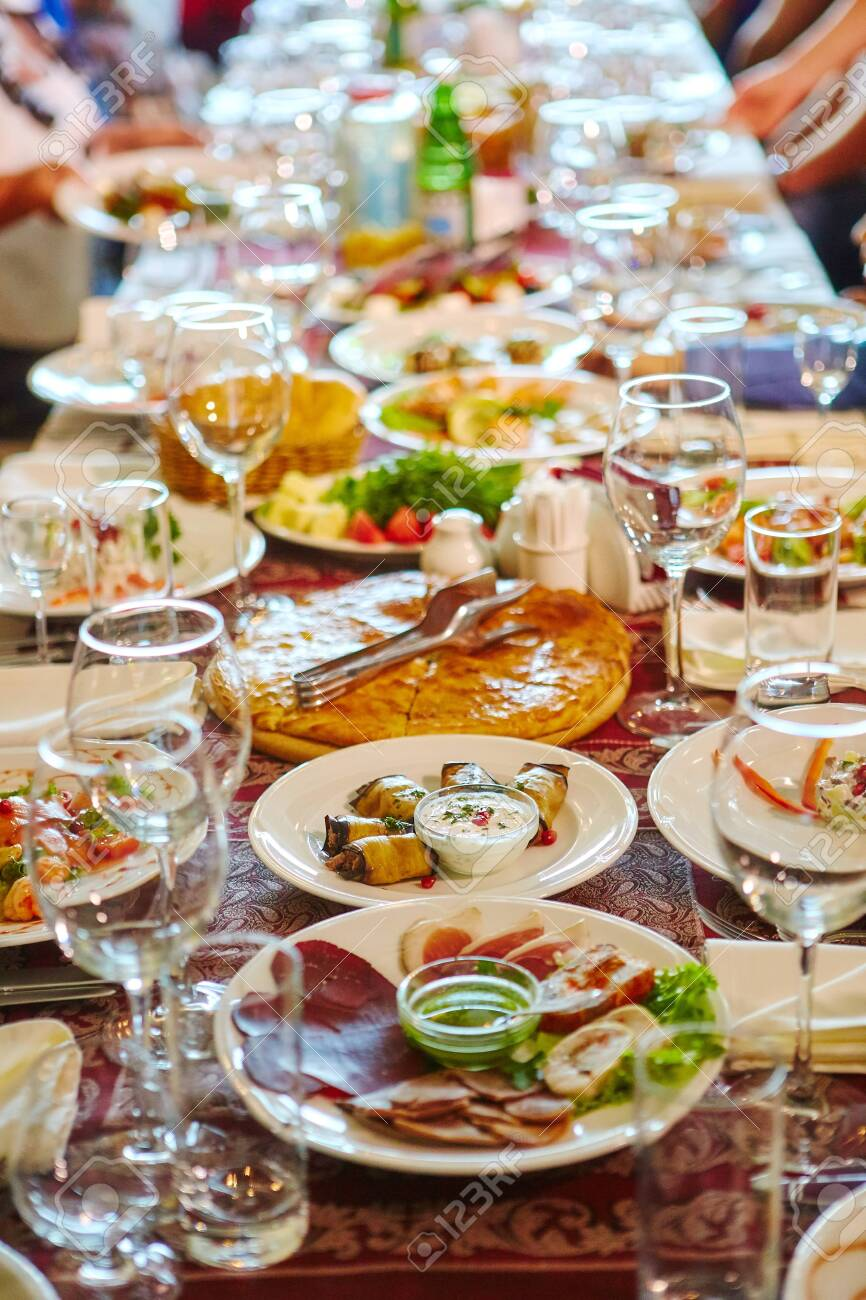 Long Banquet table. Drinks and snacks on the table. People are sitting at the table. Concept of joint celebrations. - 143080494