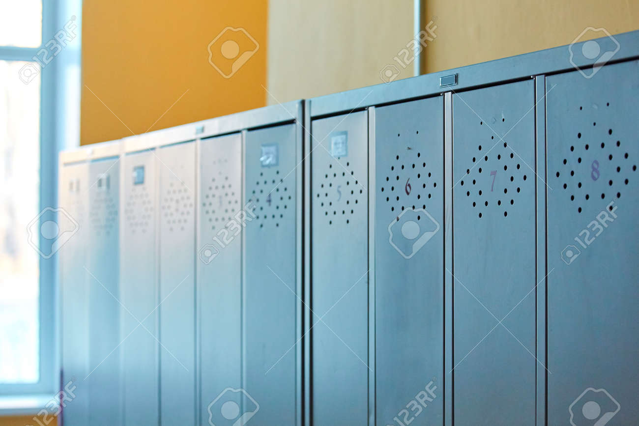 Gray metal outdated lockers in the empty school corridor of the old school. - 158596243