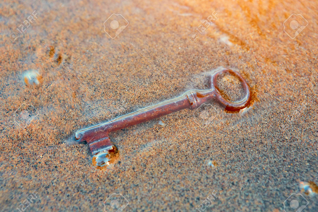 The sea washed up on the sandy beach an old vintage key to a treasure chest. The concept of success, luck and wealth. - 158596247