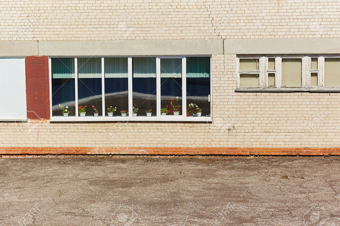 The wall of the old brick building, with a window with wooden frames, on the windowsill is blooming geranium. - 158596252