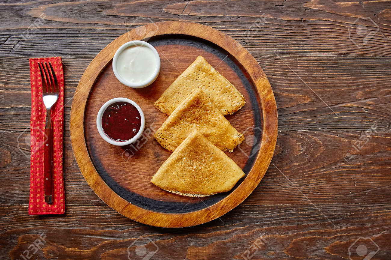 Homemade hot delicious pancakes with sour cream and jam on a wooden plate, top view - 158596254