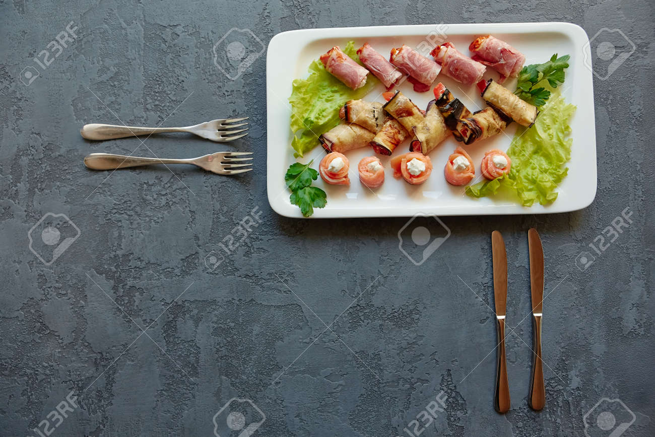 Three types of appetizers on a platter-mini canapes of red fish, eggplant rolls and ham with filling, on a beautiful gray background with forks. Place for copy space. - 158596256