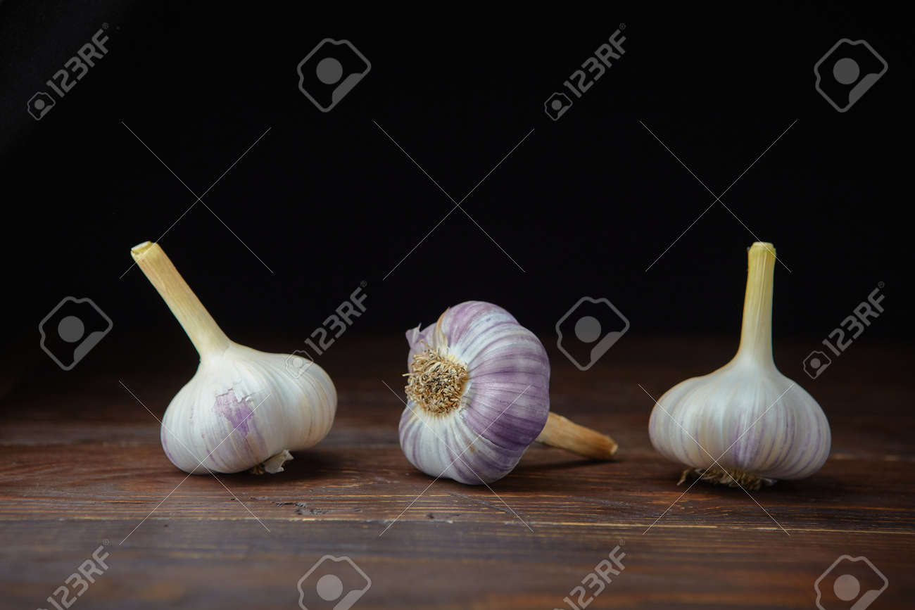 Three ripe heads of fresh garlic on a dark wooden background. Folk medicine for viral and colds. - 158596260