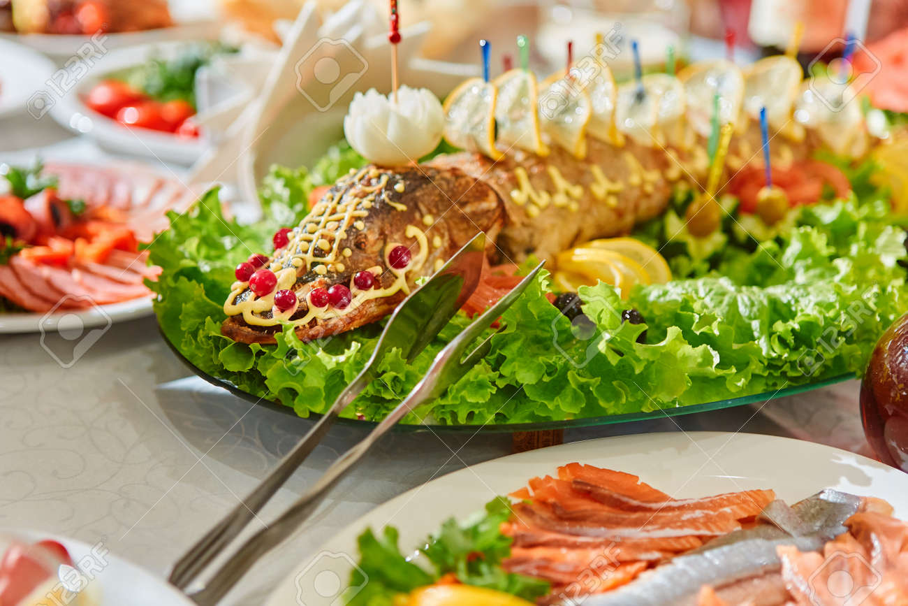 Russian national cuisine-stuffed pike on an oval dish, cooked baked fish, decorated with herbs, lemons, cranberries. - 158596264
