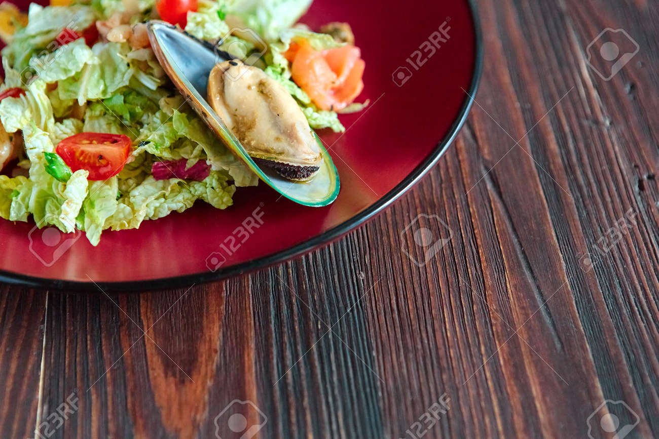 Seafood salad with citrus in a round plate on a gray textured background. - 158618841