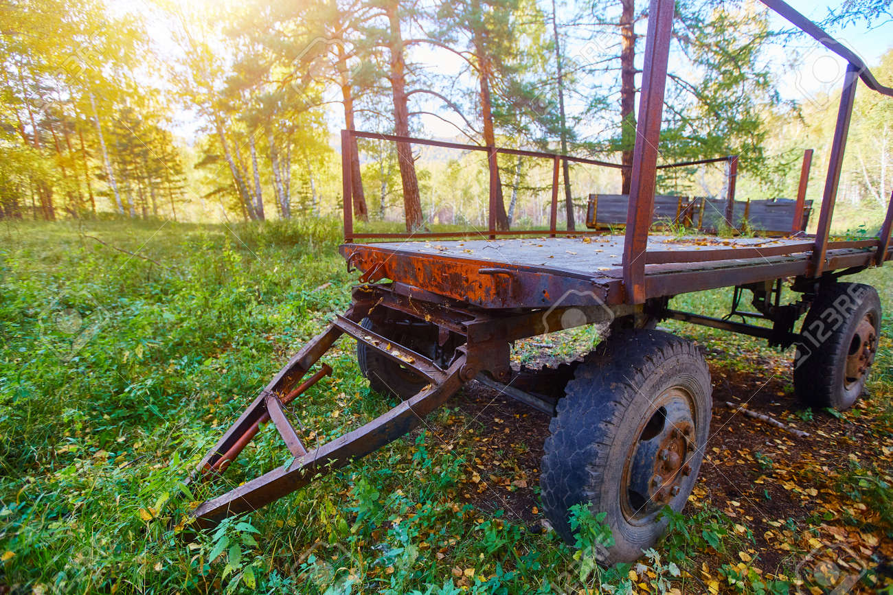 Tractor trailer. An old trailer sits on a green lawn - 158639524